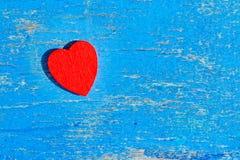La madera roja del corazón miente en un viejo tablero de madera con la pintura azul agrietada, vintage Fotos de archivo