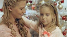 La madre abraza a su pequeña hija en una atmósfera de la Navidad Imagenes de archivo
