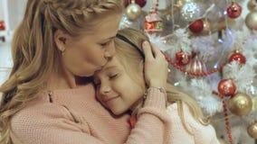La madre abraza a su pequeña hija en una atmósfera de la Navidad Foto de archivo libre de regalías
