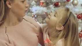 La madre abraza a su pequeña hija en una atmósfera de la Navidad Fotos de archivo libres de regalías