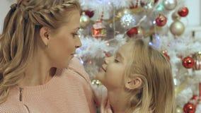 La madre abraza a su pequeña hija en una atmósfera de la Navidad Imagen de archivo