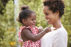 La madre afroamericana joven celebra a la hija del bebé en jardín fotos de archivo libres de regalías