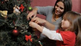La madre aiuta sua figlia ad appendere la bagattella sull'albero di Natale archivi video