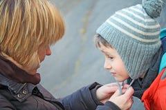 La madre aiuta suo figlio Immagine Stock