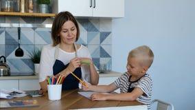 La madre aiuta suo figlio a fare i compiti in cucina Persone con concetto familiare, di stile di vita e di istruzione stock footage