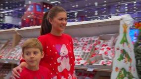 La madre alegre está abrazando a su hijo y está hablando mientras que camina a lo largo del centro comercial durante días de fies almacen de metraje de vídeo