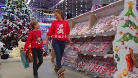 La madre alegre está hablando con su hijo mientras que camina a lo largo del centro comercial y elige regalos de Navidad almacen de video