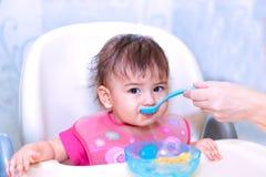 la madre alimenta al bebé con una cuchara Foto de archivo