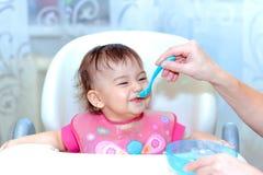 la madre alimenta al bebé con una cuchara Imagen de archivo libre de regalías