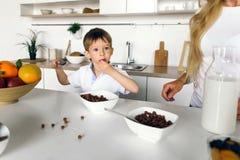 La madre alimenta al suo piccolo figlio sveglio la cucina asciutta della casa della prima colazione Fotografia Stock Libera da Diritti