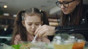 La madre alimenta a la hija con una bifurcación en un café La hija nunca quiere comer, solamente las fuerzas de la madre el nià almacen de metraje de vídeo