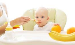 La madre alimenta il cucchiaio del bambino sulla casa della tavola Immagini Stock Libere da Diritti