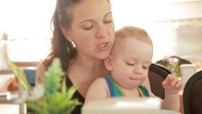 La madre alimenta il neonato sveglio con una cucchiaiata del caffè Ragazzo biondo in una maglietta verde archivi video