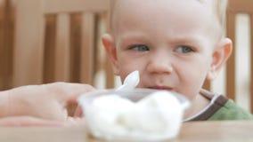 La madre alimenta il suo giovane figlio con il gelato da un cucchiaio Stanno sedendo in un caffè della via Il ragazzo realmente g archivi video