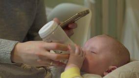 La madre alimenta il telefono del bambino video d archivio