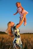 La madre alleva il bambino sulle mani nel campo wheaten Immagini Stock