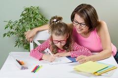 La madre amorosa che aiuta il suo allievo della scuola elementare della figlia scrive in suo taccuino, a casa alla tavola Fotografie Stock