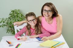 La madre amorosa che aiuta il suo allievo della scuola elementare della figlia scrive in suo taccuino, a casa alla tavola Immagine Stock