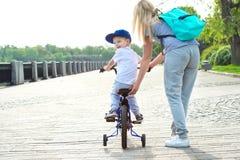 La madre aprende a su pequeño hijo para montar una bicicleta foto de archivo
