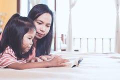 La madre asiática y la hija de la familia feliz leyeron un libro juntas Imágenes de archivo libres de regalías