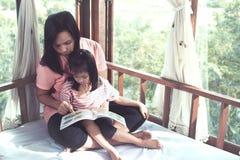 La madre asiática y la hija de la familia feliz leyeron un libro juntas Imagen de archivo