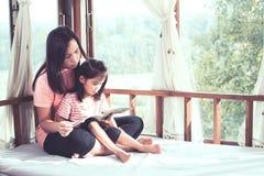 La madre asiática y la hija de la familia feliz leyeron un libro juntas Foto de archivo
