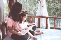 La madre asiática y la hija de la familia feliz leyeron un libro juntas Imagen de archivo libre de regalías
