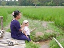 La madre asiática y su pequeño bebé gozan el pasar del tiempo junto en un campo del arroz fotografía de archivo