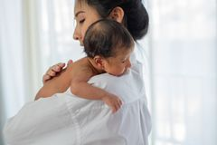 La madre asiatica con il posto bianco della camicia sopra la spalla di poco neonato dopo dare il latte ed il bambino sembrano son fotografia stock