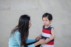 La madre asiatica del primo piano sta confortando suo figlio gridante sul fondo strutturato di marmo della parete di pietra fotografia stock libera da diritti