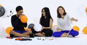 La madre asiatica della famiglia ed i suoi bambini si uniscono per la preparazione del pallone operato decorano per Halloween stock footage