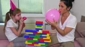 La madre ayuda a los globos del soplo de la hija almacen de metraje de vídeo