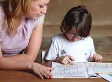 La madre ayuda a su hijo con la preparación Fotografía de archivo