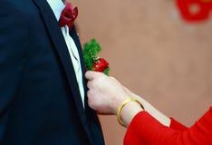 La madre ayuda a su hijo que sea el novio para llevar su ramillete de la boda en el traje del ` s del novio fotos de archivo libres de regalías