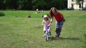 La madre ayuda a sus 4 años de la hija para montar la bici a través de prado del parque almacen de metraje de vídeo