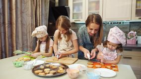 La madre ayuda a sus hijas a adornar las galletas con el esmalte almacen de video