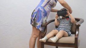 La madre ayuda a una muchacha a sacar los vidrios de la realidad virtual metrajes
