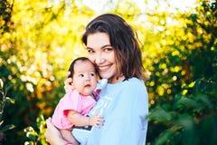 la madre bella giovane con capelli scuri tiene la sua ragazza di neonato Fotografie Stock Libere da Diritti