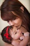 La madre besa al bebé Fotografía de archivo