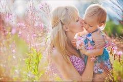 La madre besa suavemente a su hija en un campo en un fondo de fotografía de archivo