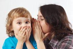 La madre bisbiglia il segreto al suo piccolo figlio Fotografie Stock