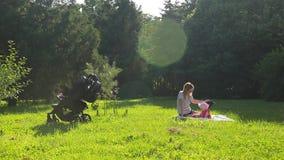 La madre bonita joven en vidrios y sombrero se sienta con su hija pequeña en césped verde en parque ilustrado de la ciudad con lo metrajes