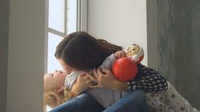 La madre bonita juega con su pequeño bebé cerca de la ventana almacen de metraje de vídeo