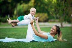 La madre bonita juguetona está haciendo entrenamiento con el pequeño hijo Se divierte el concepto, tiempo de verano fotografía de archivo