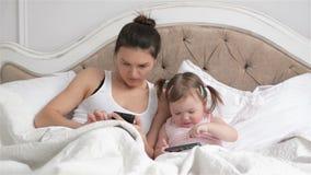 La madre bonita y su hija linda con dos colas de caballo está utilizando los artilugios juntas que mienten en la cama blanca Herm almacen de video