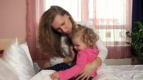 La madre calma la sua ragazza preoccupata poco del bambino abbracciando l'abbraccio a letto stock footage