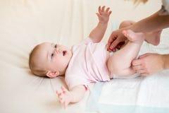 La madre cambia el pañal de su niño del bebé fotos de archivo libres de regalías