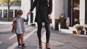 La madre camina así como niño pequeño Hermanas que llevan a cabo las manos Cámara lenta La mujer bastante europea pasa tiempo con almacen de metraje de vídeo