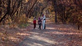 La madre camina en parque del otoño con los niños metrajes