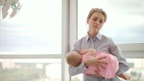La madre cansada que celebra al bebé en las manos acerca a la ventana Bebé que lleva de la madre del negocio almacen de video